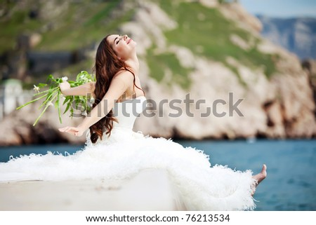 Beautiful bride by the sea - stock photo