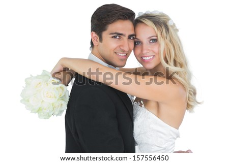 Beautiful bride embracing her husband holding a white bouquet  - stock photo