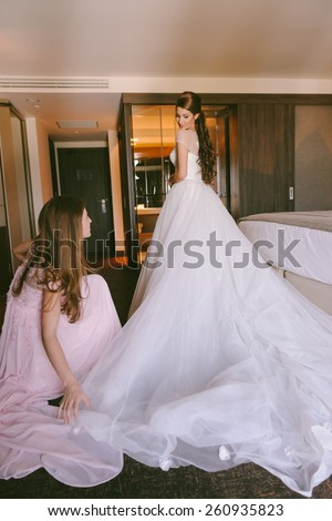 Beautiful bride getting dressed by her best friend in her wedding day
