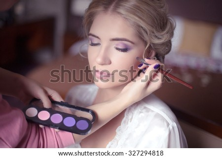 Beautiful bride girl with  wedding makeup and hairstyle. Stylist makes make-up bride on wedding day. portrait of young woman at morning. - stock photo