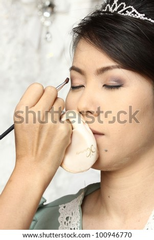 beautiful bride having her makeup for wedding day