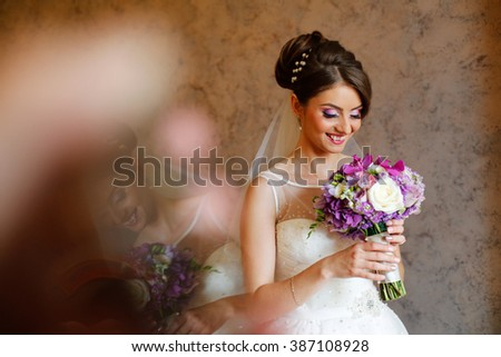 Beautiful bride holding colorful bouquet - stock photo