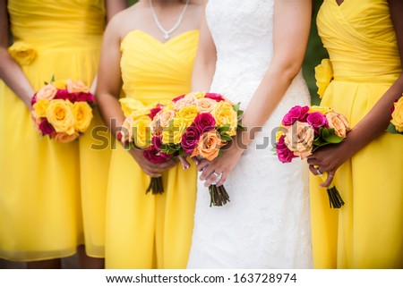 Beautiful bride holding red, yellow, orange bouquet with bridesmaids in the background. - stock photo