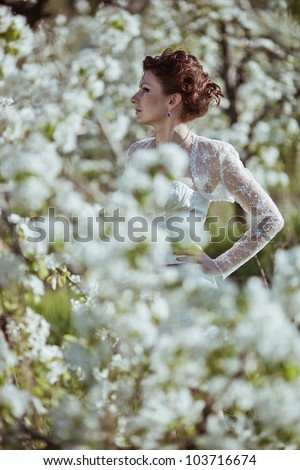 beautiful bride in a blossoming garden - stock photo