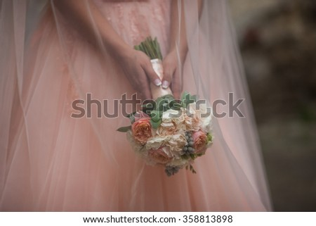Beautiful bride in a pink dress holding a bouquet and hiding under her veil outdoors - stock photo