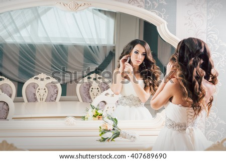 Beautiful bride in a wedding dress getting ready for the wedding dress before the mirror earrings. - stock photo