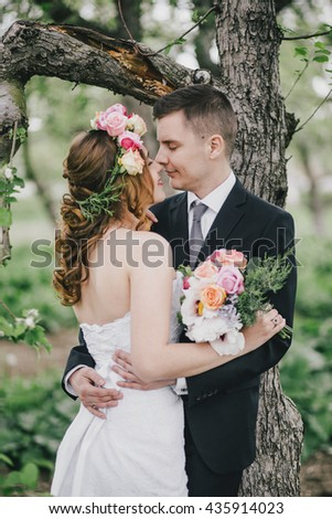 Beautiful bride in a wedding dress with bouquet and roses wreath posing with groom wearing wedding suit. Wedding day