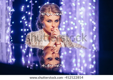 beautiful bride in a white dress image against a bright background at night Portrait of a girl. Reflection. Cold. Glowing background. Wedding