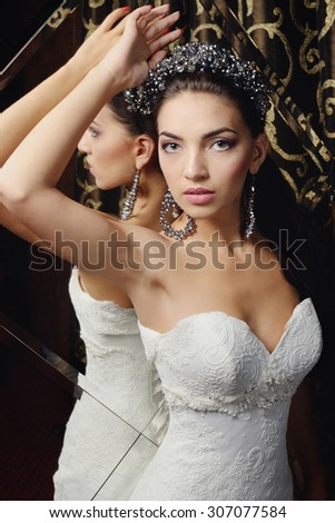 beautiful bride in an elegant dress posing in a luxurious room