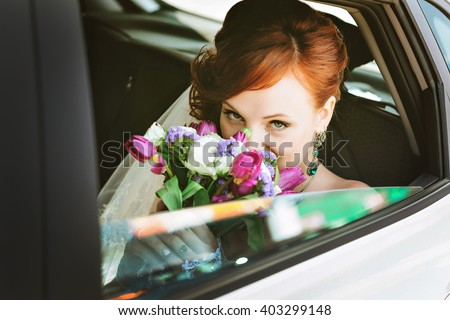 Beautiful Bride in Car on wedding day looking  - stock photo