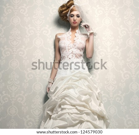 Beautiful bride in elegant white wedding dress with hand to veil - stock photo
