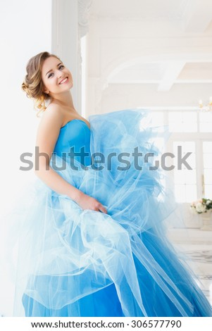 Beautiful bride in gorgeous blue dress Cinderella style in a morning - stock photo