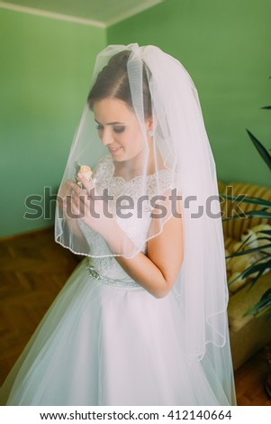 Beautiful bride in  lace wedding dress and veil looking  at the buttonhole of roses indoors - stock photo