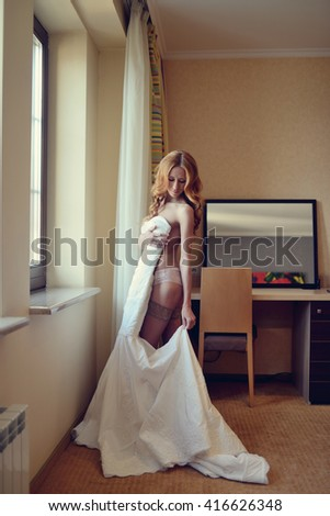 Beautiful bride in lingerie is wearing a wedding dress. Beauty model girl in white underwear. Female portrait in bridal gown for marriage. Woman with curly hair and lace veil. Cute lady indoors