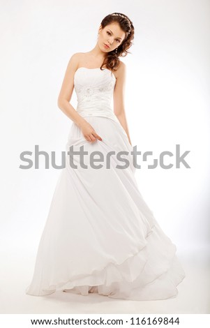 Beautiful bride in luxurious white wedding long dress posing - stock photo