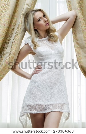 Beautiful bride in luxury hotel room with wedding dress