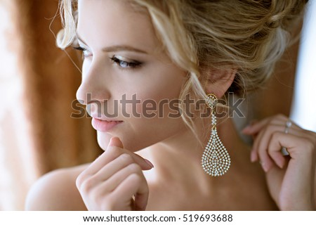 Beautiful bride in puts on earring. Beauty model girl is wearing jewelry for marriage. Wedding female portrait. Woman with curly hair and lace veil. Cute lady indoors