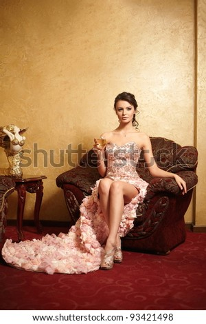Beautiful bride in unusual wedding dress in the interior sitting in armchair with a cup of wine