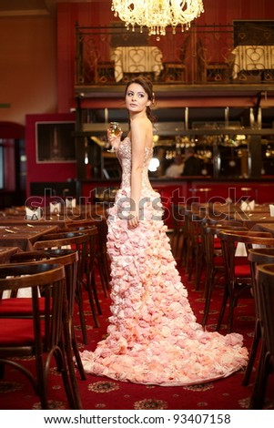 Beautiful bride in unusual wedding dress in the restaurant with cup of wine - stock photo