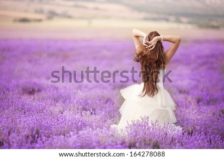 Beautiful Bride in wedding day in lavender field. Newlywed woman in lavender flowers. Young woman in wedding dress outdoors.