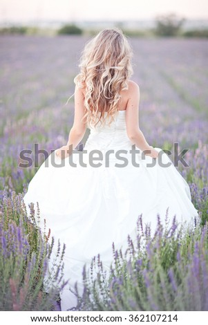 Beautiful Bride in wedding day in lavender field. Newlywed woman in lavender flowers. Young woman in wedding dress outdoors. - stock photo