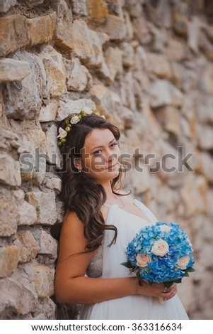 Beautiful bride in wedding dress,  near old castle - stock photo