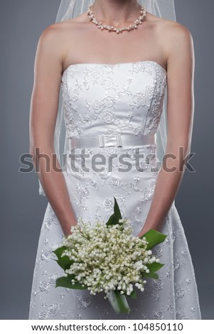 beautiful bride in white dress with bouquet studio shot - stock photo