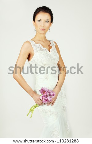 Beautiful bride in white gown with bouquet - stock photo