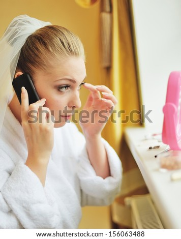 Beautiful  bride is getting ready in the morning, having make up, talking on the phone