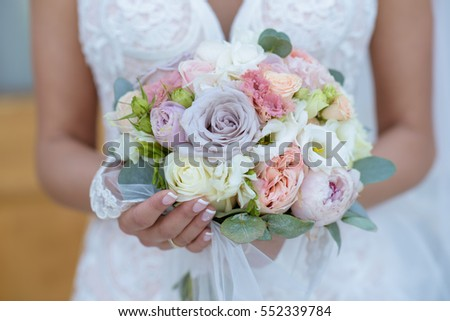 Beautiful bride is holding a wedding colorful bouquet. Beauty of colored flowers. Close-up bunch of florets. Bridal accessories. Female decoration for girl. Details for marriage and for married couple