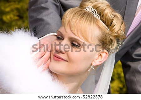 Beautiful bride is looking at the bride's wedding ring. Newlywed outside. - stock photo