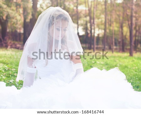 Beautiful bride is sitting on the grass in the garden
