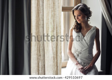Beautiful bride is sitting on the window