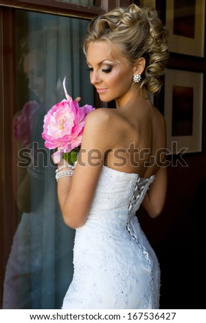 Beautiful bride is standing at the window with bunch of flowers.