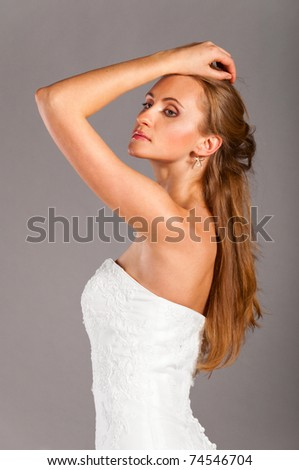 beautiful bride is standing in wedding dress on grey background and looking sideways