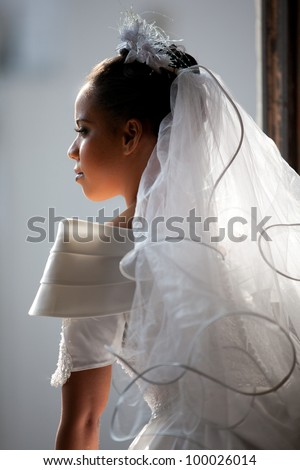 Beautiful Bride lit up from light showering her from the open window - stock photo