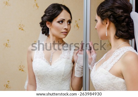 Beautiful bride near mirror - stock photo