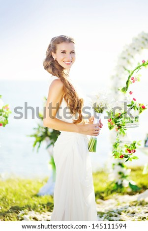 beautiful bride near the arch of flowers - stock photo