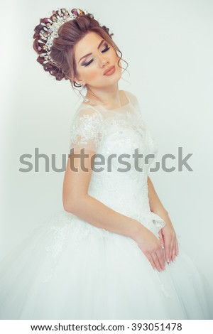 beautiful bride on a white background, young charming bride looks into camera, isolated, beautiful  girl in white wedding dress with hairstyle and bright makeup on white background - stock photo
