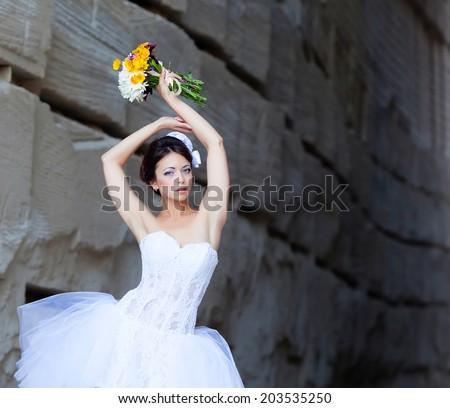 Beautiful bride outdoor portrait near high stone wall - stock photo
