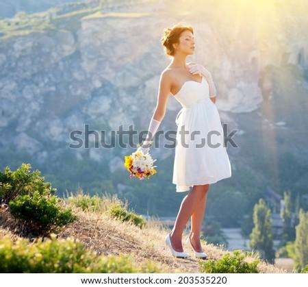Beautiful bride outdoor portrait on the mountain - stock photo