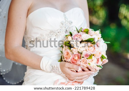 Beautiful bride outdoors. Bride holding wedding bouquet outside. Bride. Wedding hairstyle. A shot of a beautiful caucasian bride outdoor