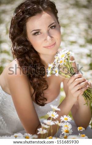 Beautiful bride outdoors in chamomile field. Bride with flowers at wedding. Young bride walking outdoors. Wedding bride on nature. Newlywed woman on outdoors. Bride with wedding makeup and hairstyle.  - stock photo