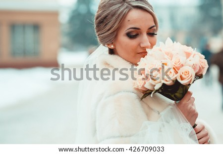 Beautiful bride portrait in winter wedding day, photo session. Bride with flowers boquet in a white fur coat