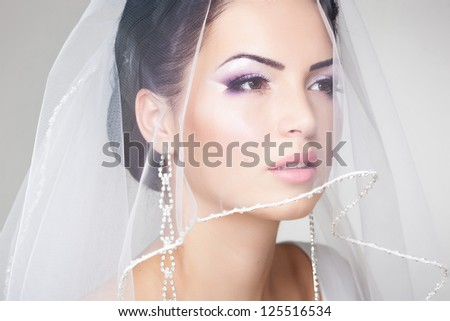 beautiful bride portrait with veil over her face, wearing professional make-up - stock photo