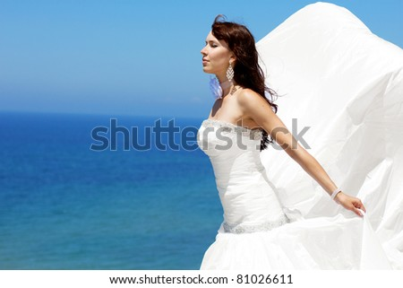 Beautiful bride posing at sea coast - stock photo