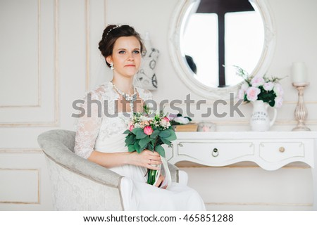 Beautiful bride posing in wedding dress. Youth. Wedding. Sofa.
