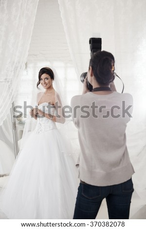 Beautiful bride posing in white room front of female photographer. - stock photo
