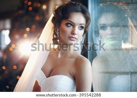 Beautiful bride posing near window, christmas tree background - stock photo