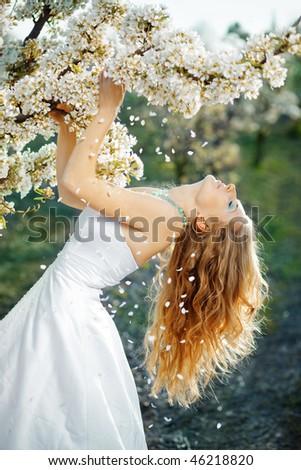 Beautiful bride posing on sky background near blossoming tree - stock photo